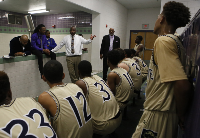 Cheyenne head coach Teral Fair speaks to his players at halftime during a boys basketball ga ...