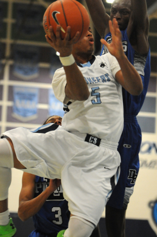 Canyon Springs Gerad Davis (5) goes up for a shot against Desert Pines Nate Grimes (24) and ...