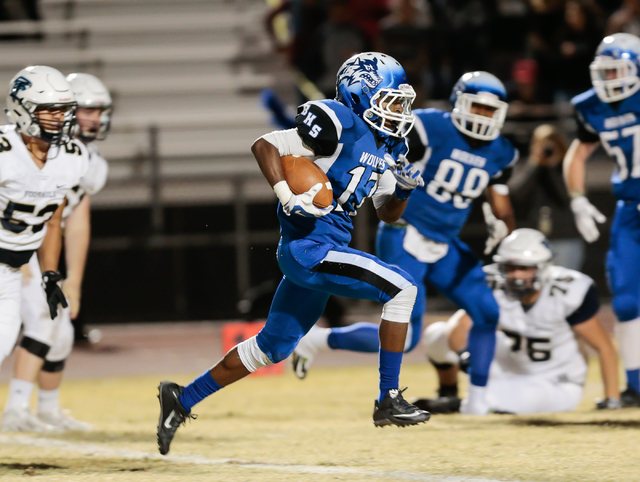 Basic senior Quison Owens (17) runs the ball as Foothill defensive players look on, during ...