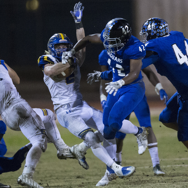 Moapa Valley's Jacob Leavitt (2) is tackled by Desert Pines' Jautae Collins (42) ...