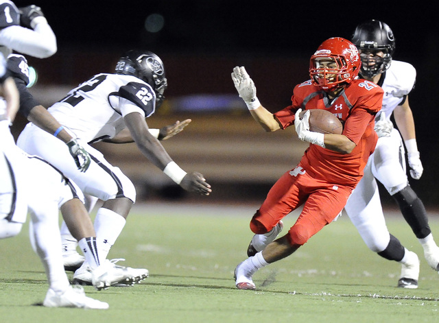 Arbor View center running back Charles Louch (21) looks for running room as Palo Verde lineb ...