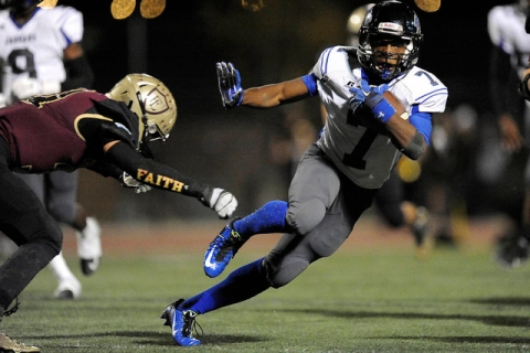 Desert Pines sophomore running back Isaiah Morris sidesteps a tackle attempt by Faith Luther ...