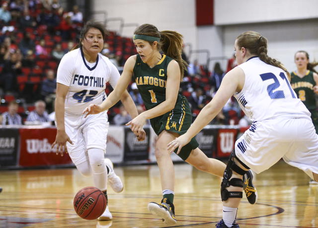 Bishop Manogue guard Katie Turner (1) drives to the basket between Foothill's Trinity ...