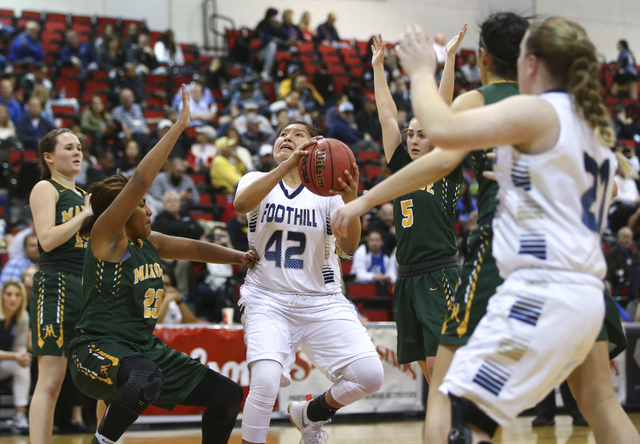 Foothill's Trinity Betoney (42) drives to the basket between Bishop Manogue defends du ...