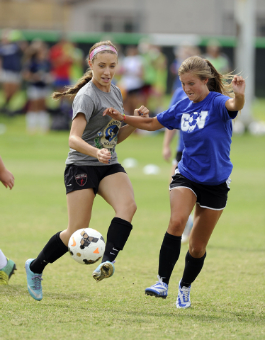 Green Valley girls soccer player Alexis Kirson, left, passes the ball in front of Madison Ho ...