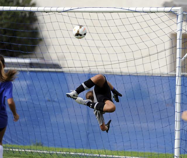 Green Valley girls soccer freshman goalkeeper Ryan Sabol tips a shot while diving backwards ...