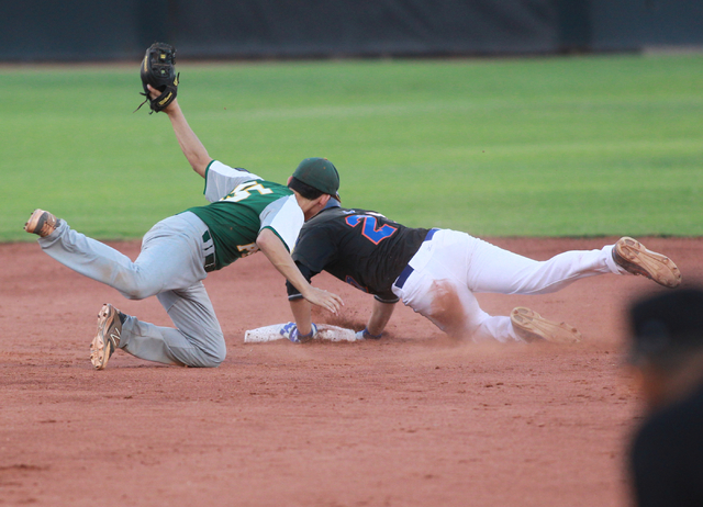 Bishop Gorman's Grant Robbins (27) dives safely into second base past Rancho's B ...