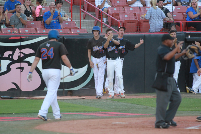 Bishop Gorman players celebrate after teammate Grant Robbins, not pictured, scores a run aga ...