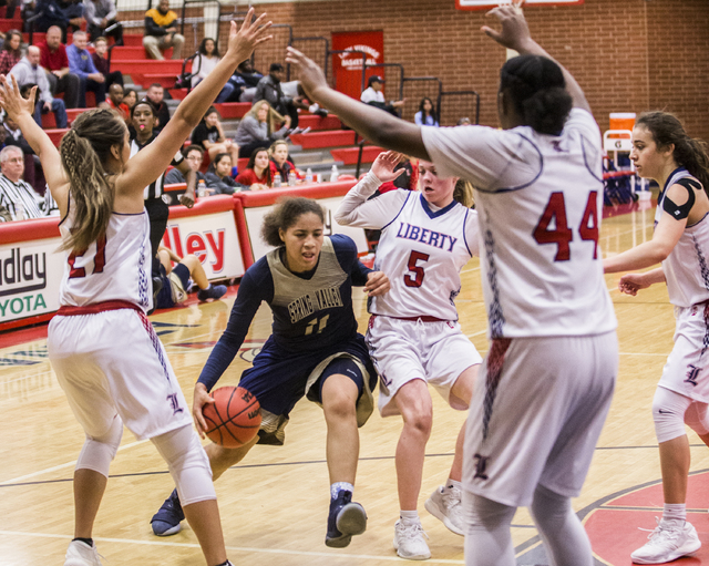 Spring Valley's Kayla Harris (11) drives past Liberty's London Pavlica (5) and K ...