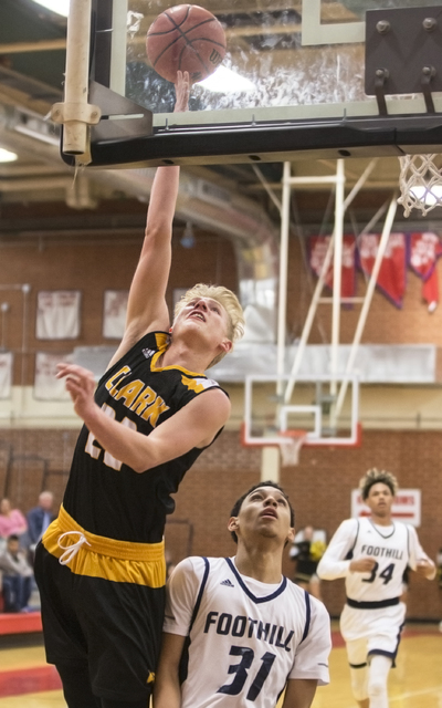 Clark's Trey Woodbury (22) slices to the basket past Foothill's Marvin Coleman ...