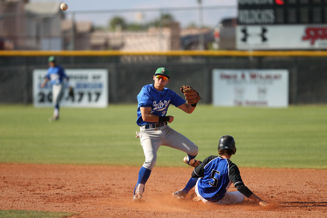 Green Valley's Jarod Penniman (2) throws to first base for a double play after taking ...
