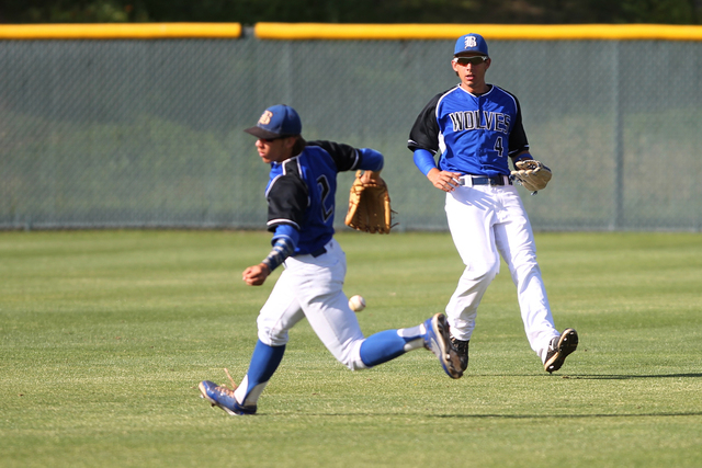 Basic's Cory Wills (2) misses a fly ball in the outfield with Logan Green (4) in the s ...