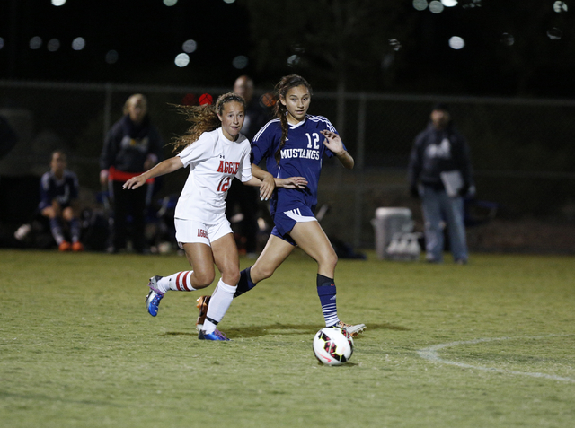 Arbor View's Hayley Vicente (12) and Shadow Ridge's Casey Childers (12) close in ...