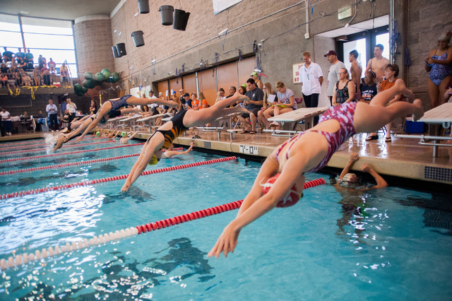 The girls dive in for the start of the 200-yard individual medley race at the Sunset Region ...