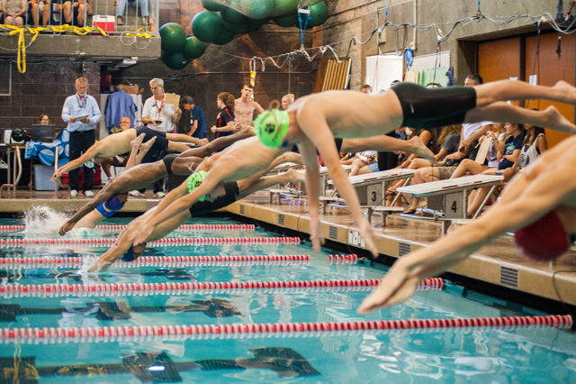 The boys dive in for the start of the 200-yard individual medley race at the Sunset Region m ...
