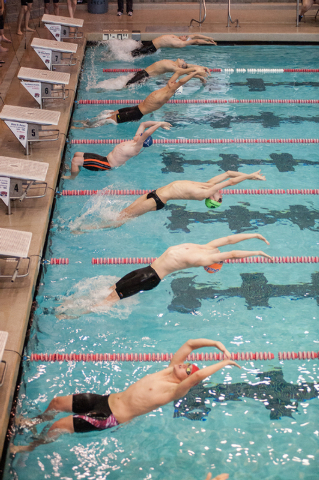 The boys dive in for the start of the 200-yard medley relay race at the Sunset Region meet o ...