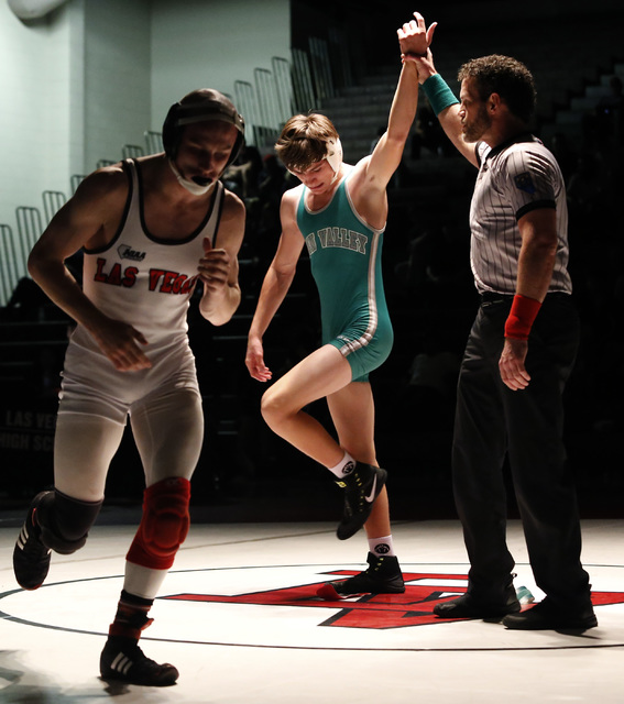 Green Valley's Justus Scott, green singlet, hand is raised as Las Vegas's Daniel ...