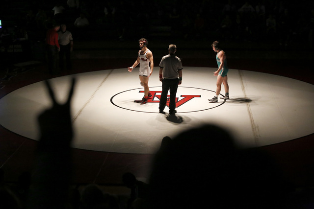 A fan signals to a referee to award Green Valley's Cody Chamblerlin, right, two points ...