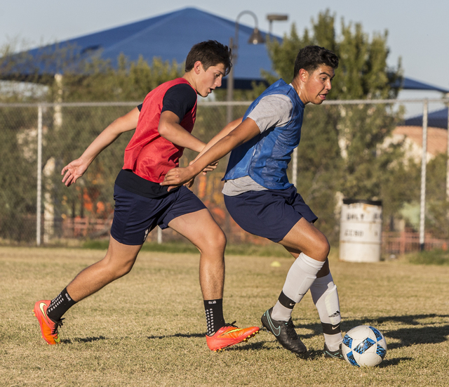 Spring Valley soccer player Jose Lopez, right, dribbles past a defender during practice on ...