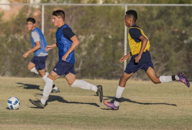 Spring Valley soccer player David Van Hoose, center, sprints past a defenders during practic ...