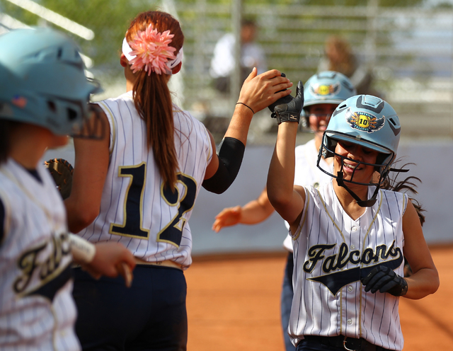 Foothill's Vanessa Parrales high fives teammate Sarah Maddox (12) after scoring a run ...