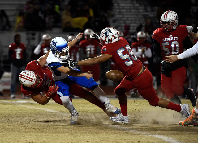 Basic quarterback Rasheem Newsome (8) fumbles the ball under pressure from Liberty during a ...
