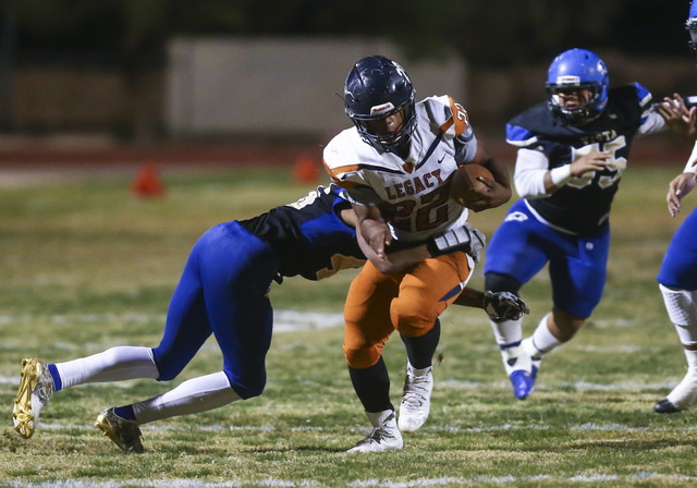 Legacy's Samuel Turner (22) is tackled by Sierra Vista's Kevin McCray (46) durin ...