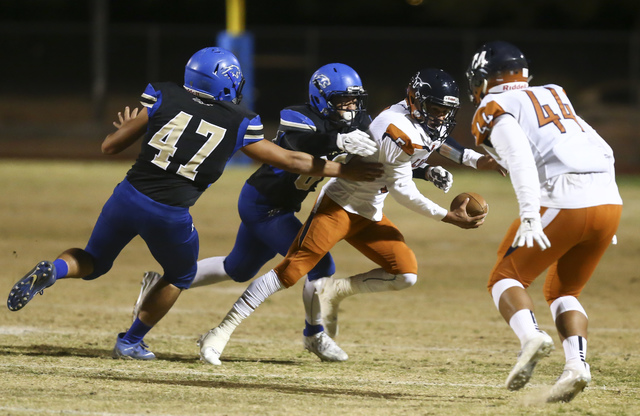 Legacy quarterback Roberto Valenzuela (5) tries to avoid being tackled by Sierra Vista defen ...