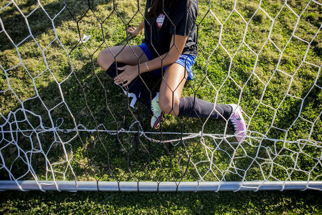 A Western Warriors girls soccer teammate helps set up the net before practice at Western Hig ...