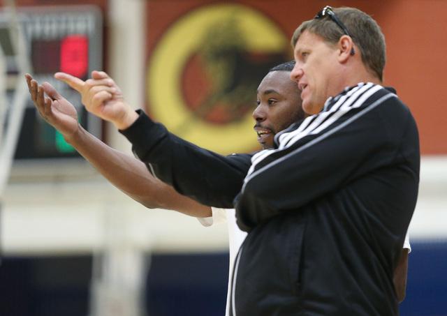Clark High School basketball head coach Colin Darfour, left, talks to an assistant coach dur ...