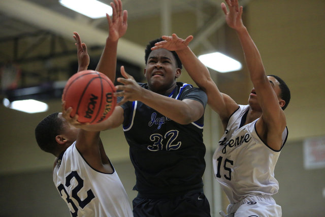 Desert Pines senior Derrick Coleman (32) tries to shoot the ball between two defenders durin ...