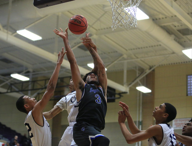 Desert Pines senior Trevon Abdullah (3) is fouled while taking a shot during the Class 3A bo ...