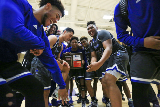 The Desert Pines High School Jaguars dance with a regional trophy after beating Cheyenne Hig ...