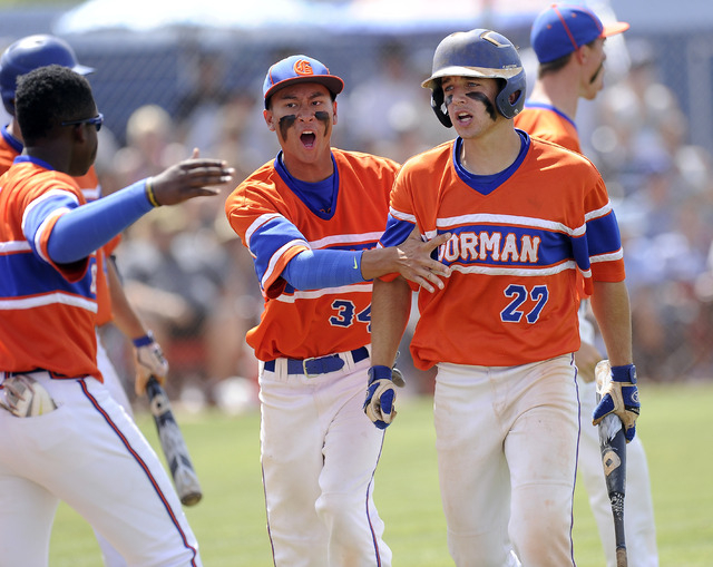 Bishop Gorman's Grant Robbins (27) is congratulated by teammates after scoring a run i ...