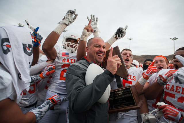 Bishop Gorman head coach Tony Sanchez celebrates with his team after winning the NIAA Divisi ...