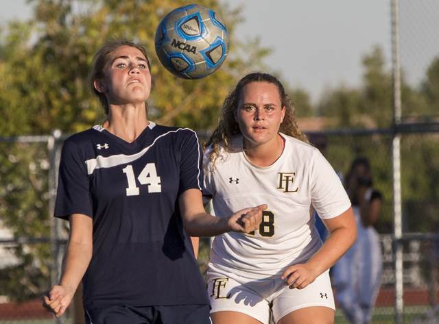 Centennial's McKenna Stratton (14) fights for a ball with Faith Lutheran's Brook ...