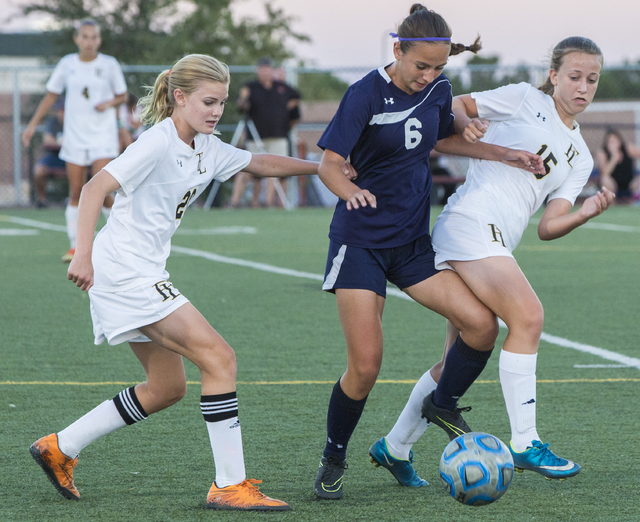 Centennial's Lauren Levoyer (6) fights for a ball with Faith Lutheran's Amelia M ...