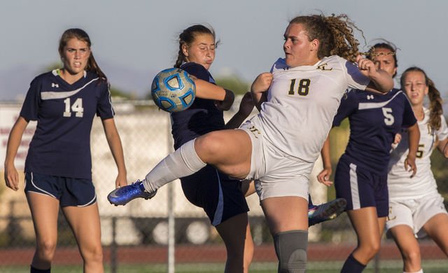 Faith Lutheran's Brooke Nigro (18) fights for a ball with Centennial defenders at Fait ...