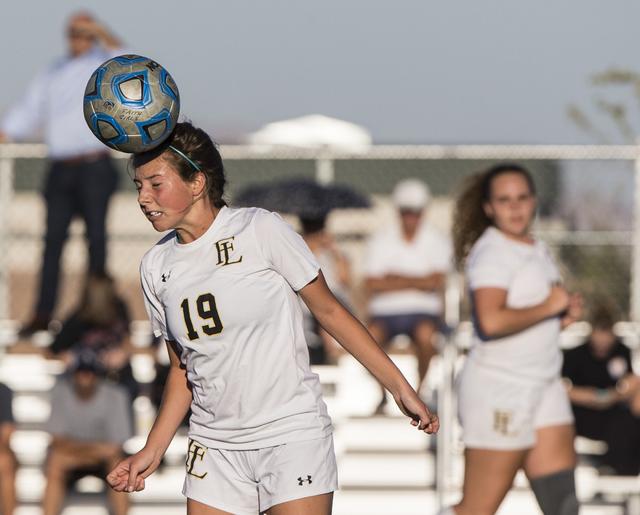 Faith Lutheran's Nikki Amavisca (19) heads a ball out of danger during her team' ...