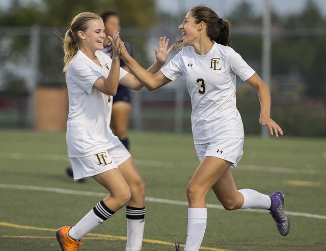 Faith Lutheran's Isabella Gutierrez (3) celebrates with teammate Amelia McManus (20) ...