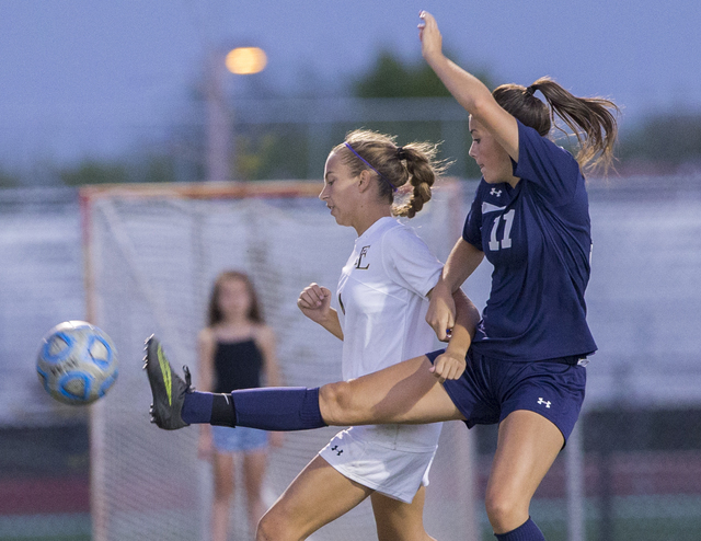 Centennial's Amanda Page (11) fights for a ball with Faith Lutheran's Megan Sone ...