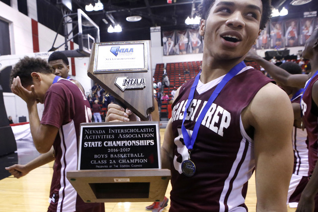 Agassi Prep's Allen Merritt (5), right, holds the championship trophy after him and hi ...