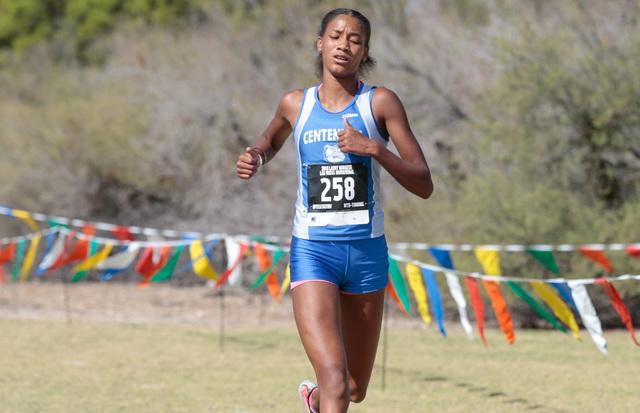 Centennial High School cross country runner Alexis Gourrier (258) runs across finish line to ...