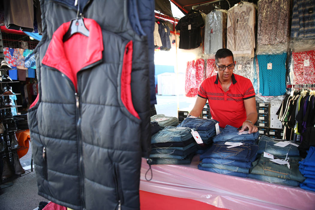 Vendor Adrian Reyes organizes merchandise at his clothing booth at the Broadacres Marketplace i ...