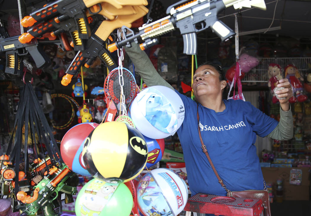 Irene Flores, owner of Factory Toys, prepares for business at the Broadacres Marketplace in Nor ...