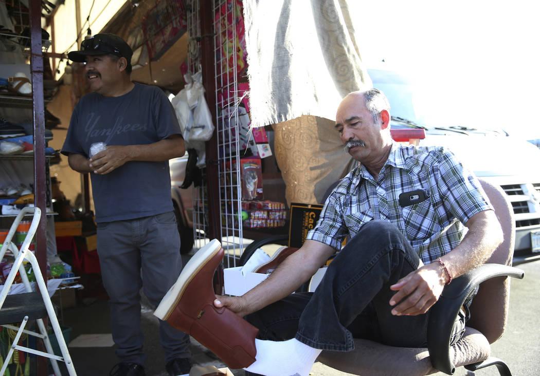 Vendor Javier Rivas, left, helps Pedro Ortega find pair of boots at the Broadacres Marketplace ...