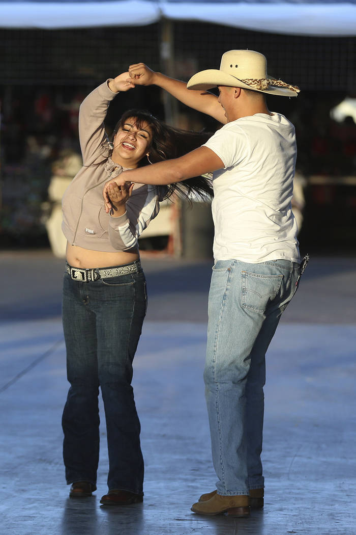 Jackie Canizales, 19, left, and her brother Jessie, 16, of Las Vegas, dance to live music at th ...
