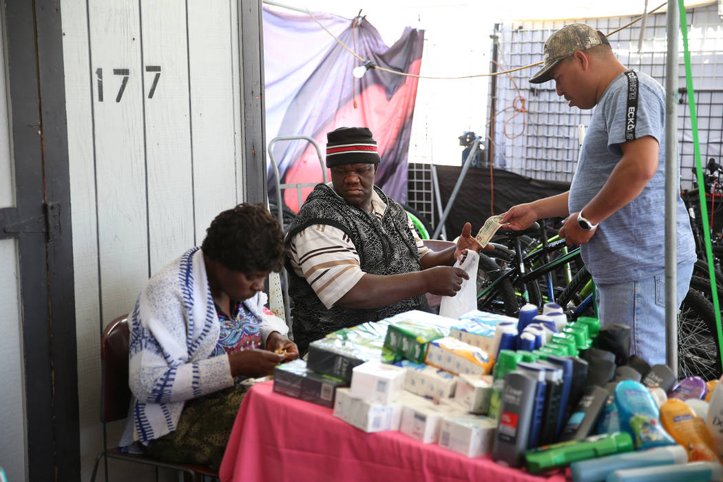 Javier Espino, right, of Las Vegas, buys hygiene products from Wilbert Talice, center, and his ...