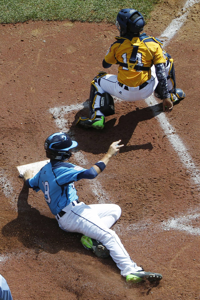 Las Vegas' Zach Hare, bottom, scores behind Chicago catcher Brandon Green (14) on a single by B ...