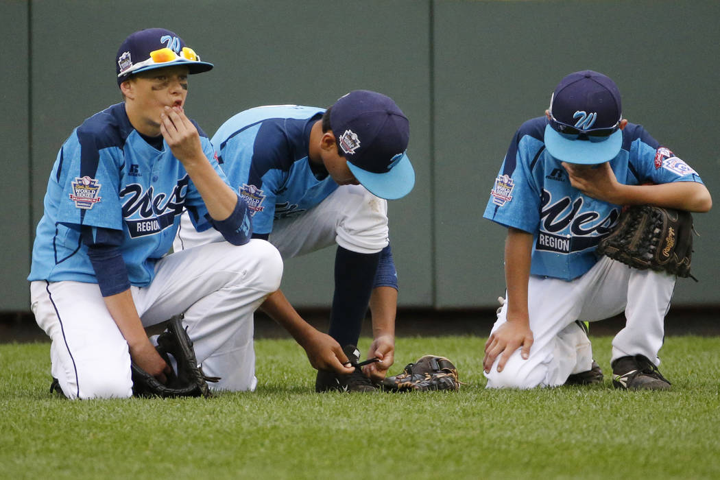 Las Vegas' Dallan Cave, left, Alex Barker, center, and Zach Hare kneel in the outfield during ...